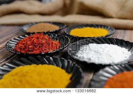 Spices in black ceramic plates on wooden background. Various spices selection. Six plates with different colorful spices top view