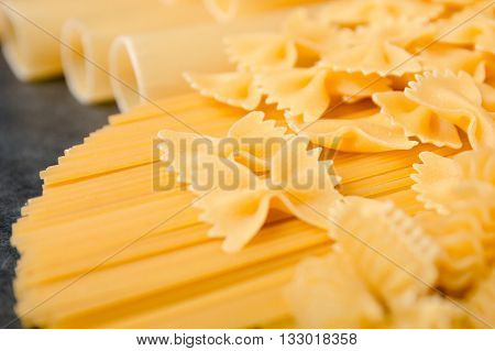 Mixed dried pasta selection on black wooden background. Variety of types and shapes of Italian pasta. Raw pasta background.