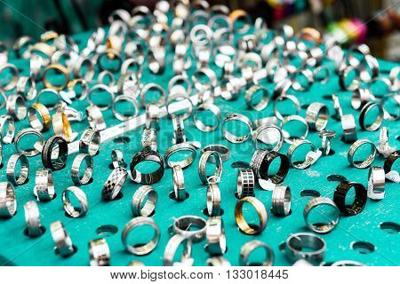 Display With Different Designs Of Handmade Silver Rings On Green Stand