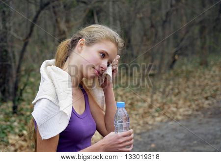 Sport girl runner is jogging on forest stop and drink of bottle water path in park.