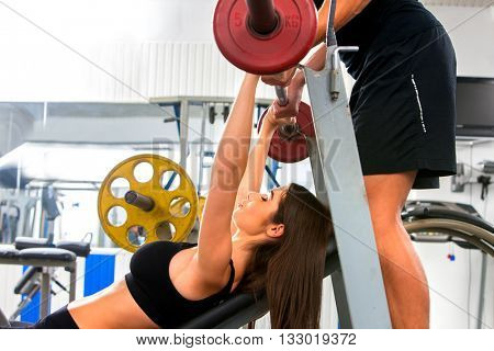 Woman working his arms and chest at gym. She lifting barbell and man back up her barbell in sport gym.