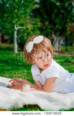 Little baby girl with Tablet sitting on the white cover in the park. Girl Using a Tablet.