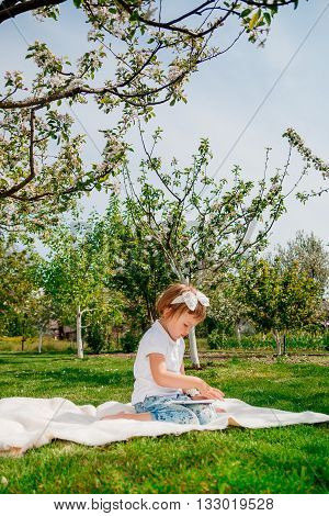 adorable blonde toddler girl dressed in white polo and jeans barefoot sitting on white blanket in park with blossoming trees in the background enjoyingplaying using tablet with touchscreen. Girl Using a Tablet.