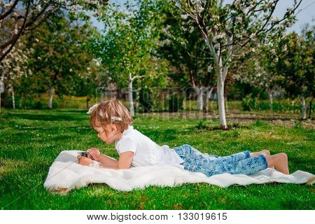 baby girl dressed in white polo and jeans barefoot lying with tablet on the fur blanket in park with blossoming trees in the background. Little girl studies on the tablet