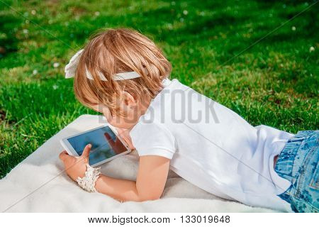 unrecognizable baby girl dressed in white polo and jeans barefoot lying with tablet on the white fur blanket in the park. Little girl play a game on tablet.