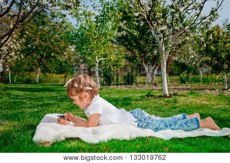 Happy baby girl dressed in white polo and jeans barefoot lying with tablet on the fur blanket in the park with blossoming trees in the background. Little girl play a game on tablet.