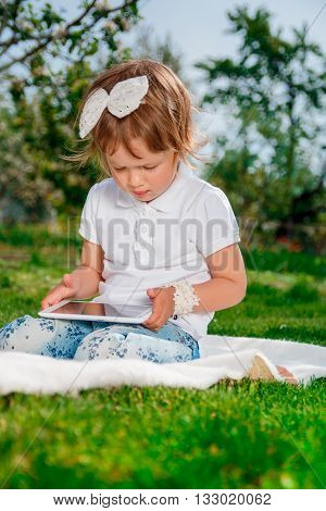 baby girl dressed in white polo and jeans barefoot sitting with tablet on the white fur cover in park. Little girl studies with the tablet