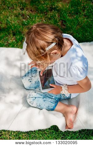 unrecognizable baby girl dressed in white polo and jeans barefoot sitting with tablet on the white fur cover in the park. Little girl play a game on tablet.
