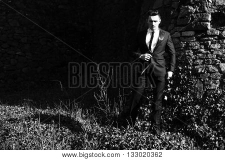 Man young handsome sensual elegant model in suit with skinny necktie poses full length looks in camera outdoor black and white on masonry background