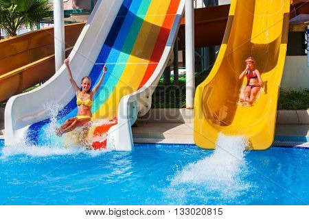 Two children on water slide at aquapark and thumb up. Summer swimming holiday. There are two water slides in aqua park. Swimming outdoor.