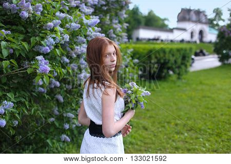 Young girl resting in a park with flowers