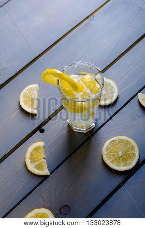 Glass Of Lemonade On Wood Between Parts Of Lemons. Lemonade With Fresh Lemon On Wooden Background.