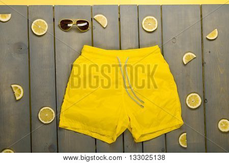 Man Beach Accessories On Wooden Background. Yellow Swim Trunks, Aviator Sunglasses Between Parts Of