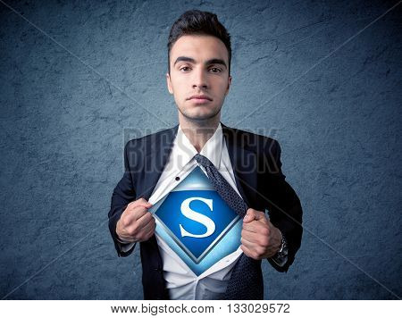 Businessman ripping off his shirt with superhero sign on his chest concept on background