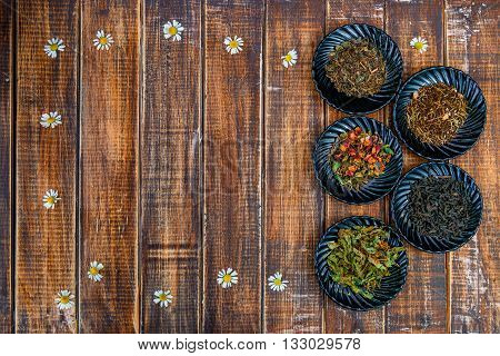 Different kinds of tea on plates on wooden background with flowers of chamomile . Assortment of dry tea. Tea concept. Tea leaves. Top view. Copy space frame.
