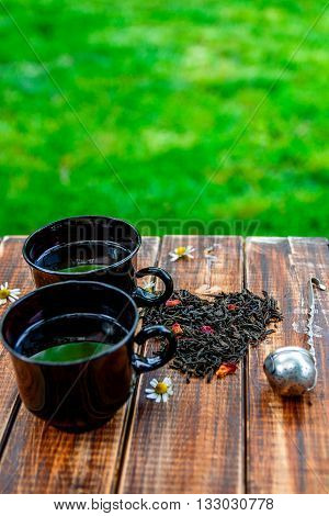 Two cup of tea near dry leaves of black tea make in heart near Vintage strainer on wooden table in garden and on nature background. Tea concept. Tea leaves. Top view. Closeup. Love. breakfast.