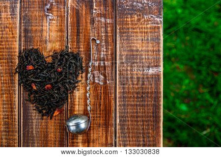 Vintage strainer near dry leaves of black tea make in heart on wooden table in garden and on nature background. Tea concept. Tea leaves. Top view. Closeup. Love. Copy space.