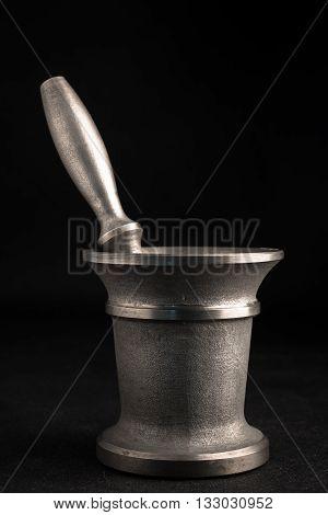 Metal mortar and pestle on black background.