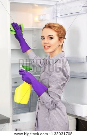 Young woman cleaning empty fridge with a sponge