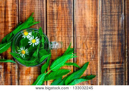 A cup of mint tea with chamomile on a wooden background. herbal tea with chamomile and fresh mint leaves on table. Copy space. Frame. Top view.