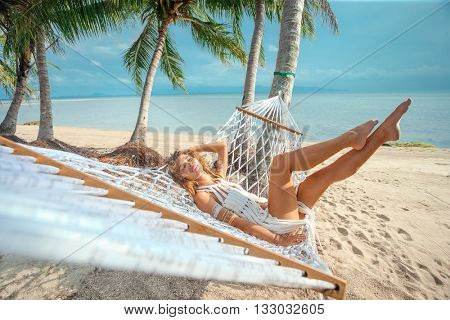 Woman relaxing on hammock with white hat sunbathing on vacation