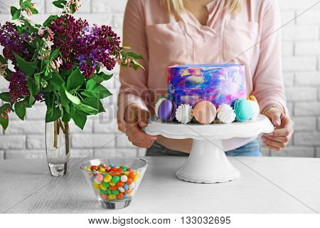 Woman decorating cake on white table