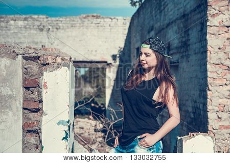 Beautiful longhaired dark-haired girl in cap torn jeans and a black T-shirt on an abandoned house. Attractive woman in jean and cup outfit posing in old ruined factory house. tone photo