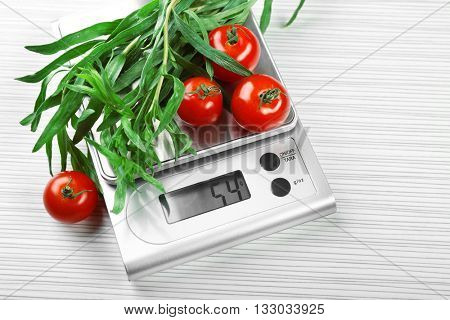 Tomatoes and tarragon with digital kitchen scales on wooden background