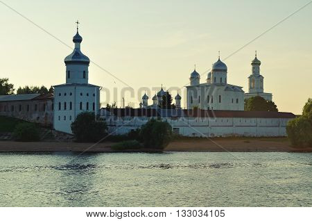 Architecture landscape - towers and cathedrals of Yuriev male monastery on the bank of the Volkhov river in Veliky Novgorod Russia sunset summer view in backlight vintage filter applied