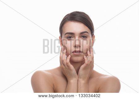 Portrait of shirtless lady touching her face over white background. Beautiful woman having elegant and perfect face. No makeup.