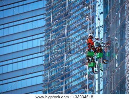 Group of workers cleaning windows at Singapore skyscraper