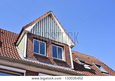 Old house with dormer. Architectural detail and blue sky. House with wooden dormer.