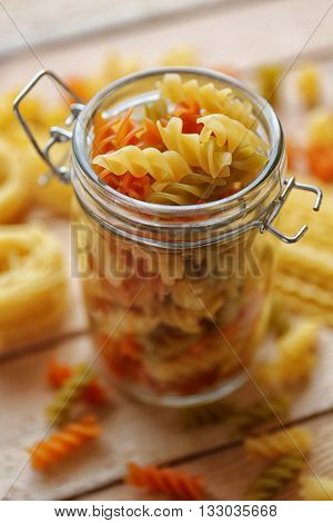 Fusilli pasta in a jar on wooden table background