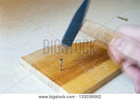 Nail hammering. A man hammering nail into wooden board