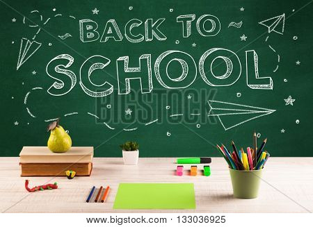 Back to school concept with writing on blackboard and desk, apple, books, items