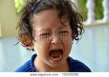 Portrait of a little toddler girl crying with mouth wide open and upset expression in the face.