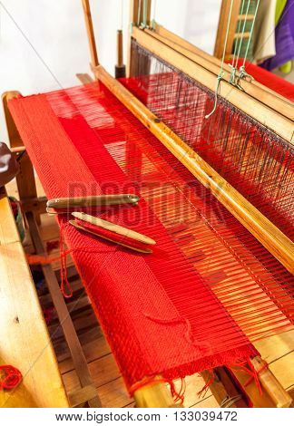 Vintage wooden loom weaving prepared for the red carpet. Wooden weaving shuttle on an old manual weaving machine