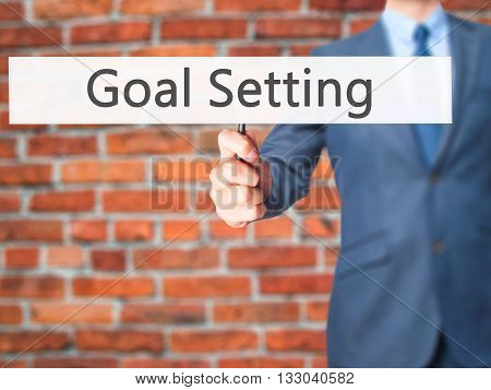 Goal Setting - Businessman Hand Holding Sign