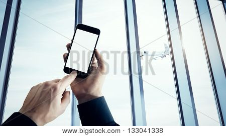 Photo businessman holding modern smartphone hand pushes button.Blank screen Isolated white, airplane take off, airport background. Ready for your private information.Business travel mockup.Horizontal