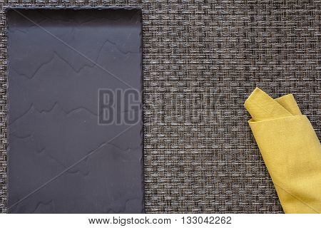 Black flat plate and mustard yellow folded napkin on woven grey thick wire warp textured background