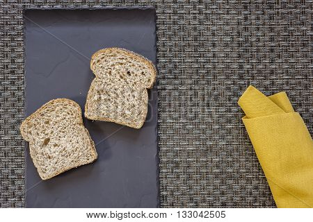 Black flat plate with two slices of bread and mustard yellow folded napkin on woven grey thick wire warp textured background