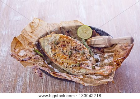 Baked fish with rosemary capers and lime on a wooden table