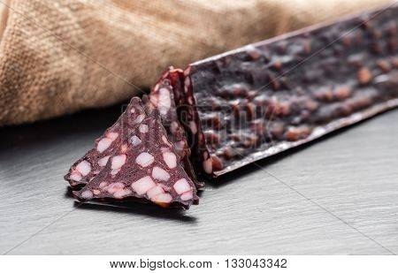 jerked sausage with fat on a dark background
