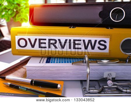 Yellow Office Folder with Inscription Overviews on Office Desktop with Office Supplies and Modern Laptop. Overviews Business Concept on Blurred Background. Overviews - Toned Image. 3D.