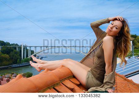Woman enjoying sunbath on the rooftop, on river bridge background.