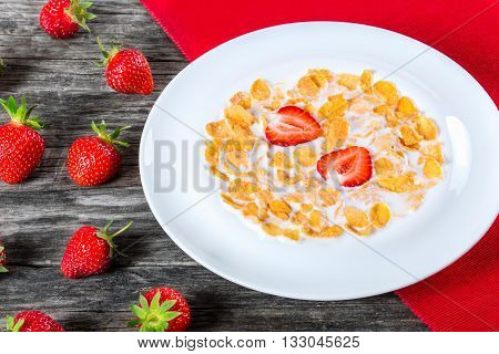 healthy corn flakes with milk and strawberries in a white dish on an old rustic table studio lights close-up view from above