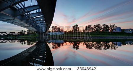 Panoramic from under the Main Street bridge at dusk with vibrant sky and smooth reflection in the river.