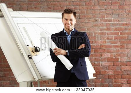 Young engineer holding blueprint near panel board on brick wall background