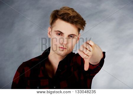Upset man with thumbs down.