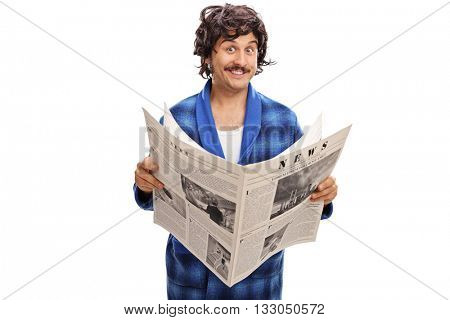 Joyful young man in a blue bathrobe holding a newspaper and looking at the camera isolated on white background